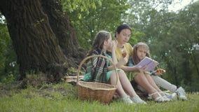 Zitting van de portret de leuke hogere vrouw op de deken onder de boom in het park die het boek lezen Aanbiddelijke twee stock videobeelden