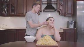 Zitting van de portret de leuke mollige vrouw in de keuken thuis De slanke blonde mensen hangende noedels op de oren van zijn vet stock videobeelden