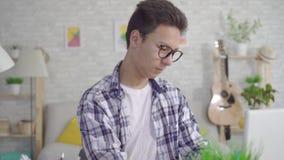 Zitting van de portret vond de jonge Aziatische mens bij laptop een oplossing voor succes op het werk of school stock video