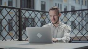 Zitting van de portret de zekere gebaarde jonge mens bij de lijst aangaande het terras voor laptop, het werken Concept van stock footage