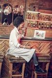 Zitting van de profiel de Afro-Amerikaanse serveerster als voorzitter dichtbij barteller royalty-vrije stock foto's