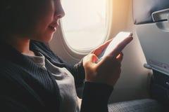 Zitting van de toeristen de Aziatische vrouw dichtbij vliegtuigvenster en het gebruiken van Smartphone tijdens vlucht stock fotografie