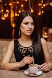 Zitting van het donkerharige de lange haar in een koffie met Stock Fotografie