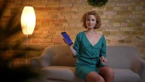 Zitting van het gember de krullend-haired Kaukasische meisje op bank en smilingly het tonen van het blauwe scherm van tablet op c stock videobeelden
