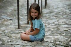 Zitting van het meisje cobbled stenen stock fotografie
