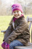 Zitting van het portret de jonge meisje in openlucht in de winter Royalty-vrije Stock Foto