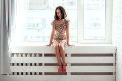 Zitting van het schoonheids de Aziatische meisje op vensterbank Royalty-vrije Stock Afbeeldingen
