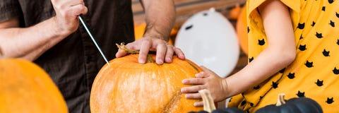 Zitting van het Unrecognisable de jonge meisje op keukenlijst, die haar vader helpen om grote pompoen te snijden Halloween-famili royalty-vrije stock foto's