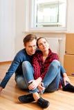 Zitting van het Yougn de gelukkige paar op de vloer in nieuw huis Stock Afbeelding