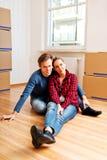 Zitting van het Yougn de gelukkige paar op de vloer in nieuw huis Stock Foto's