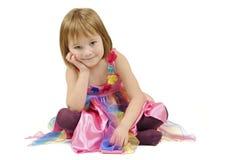 Zittingsmeisje in een kleurrijke kleding royalty-vrije stock foto