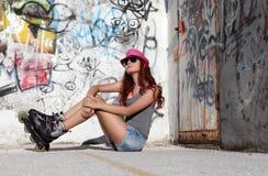 Zittingsmeisje met rolschaatsen op graffiti backgr Stock Foto's