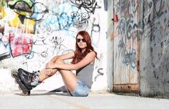 Zittingsmeisje met rolschaatsen op graffitiachtergrond Stock Afbeeldingen