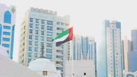 Zjednoczone Emiraty Arabskie flagi falowanie wokoło miasta linia horyzontu przeciw błyszczącemu słońcu