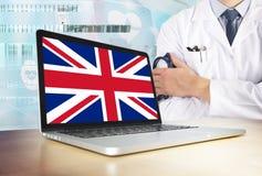 Zjednoczone Królestwo system opieki zdrowotnej w technika temacie Wielka Brytania flaga na ekranie komputerowym Doktorska pozycja zdjęcia stock