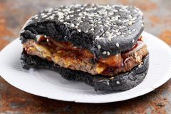 Zjedzony czarny hamburger Obrazy Royalty Free