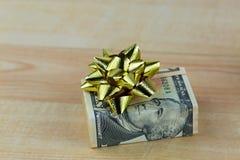 Zlany twierdzić dolarowy pieniądze banknotu rachunek z błyszczącym złotym prezentem obraz royalty free