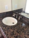 Zlew i countertop w łazience z lustrem Zdjęcia Stock