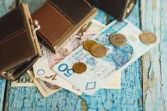 Zloty polacca con i piccoli portafogli sui vecchi precedenti di legno Fotografia Stock Libera da Diritti