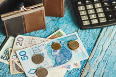 Zloty polacca con un portafoglio e un calcolatore, fondo di legno Fotografia Stock