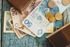 Zloty polacca con un portafoglio sui precedenti di legno Immagini Stock Libere da Diritti