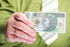 Zloty polacca dei soldi 100 della tenuta dell'uomo d'affari Immagini Stock