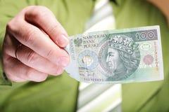 Zloty polacca dei soldi 100 della tenuta dell'uomo d'affari Fotografia Stock