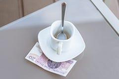 Zloty vingt polonais et tasse de café vide sur une table en verre de café extérieur Paiement, astuce photos stock
