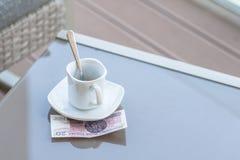 Zloty vingt polonais et tasse de café vide sur une table en verre de café extérieur Paiement, astuce photo libre de droits