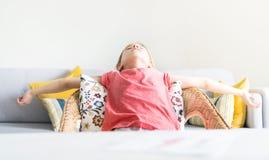 Zmęczona mała preschool dziewczyna rozprzestrzenia szerokie ręki kłama i patrzeje stropować w wygodnym krześle blisko biurka obraz stock