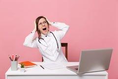 Zmęczona szalenie kobiety lekarka siedzi przy biurko pracą na komputerze z medycznym dokumentem w szpitalu odizolowywającym na pa zdjęcia stock