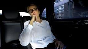 Zmęczony businesslady obsiadanie na tylnym siedzeniu samochód, iść spotykać partnerów zdjęcia stock