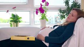Zmęczony ciężarny biznesowej kobiety lying on the beach na łóżku i muska jej dużego brzucha zbiory