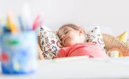 Zmęczony mały preschool dziewczyny dosypianie w wygodnym krześle blisko biurka zdjęcia royalty free