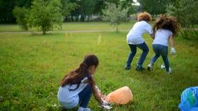 Zmęczeni ale pamiętający mali wolontariuszi współzawodniczy w cleaning zbiory