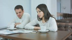 Zmęczeni partnery biznesowi pracuje na projekcie podczas lunchu przy kawiarnią zbiory wideo
