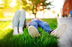 Zmęczeni ucznie cieszą się odpoczynek w jardzie kampus zdjęcia stock