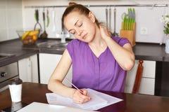 Zmęczenie urocza kobieta ból w szyi, przepracowywający się, pisze w papierach, siedzi przeciw kuchennemu inerior z takeaway kawą  obrazy royalty free