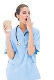 Zmęczona brown z włosami pielęgniarka w błękicie szoruje ziewanie i mienia filiżanka kawy zdjęcia royalty free