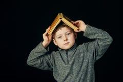 Zmęczona chłopiec trzyma książkę nad jego głową obrazy stock