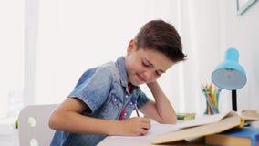 Zmęczona chłopiec z książkowym writing notatnik w domu zbiory wideo