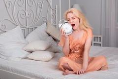 Zmęczona dziewczyna chce spać i ustawia alarm Fotografia Royalty Free