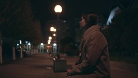 Zmęczona dziewczyna w beżowym żakiecie z szargającym włosianym odprowadzeniem na ciemnej ulicie po pracy zbiory wideo