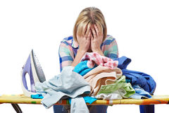 Zmęczona gospodyni domowa odprasowywający kobiet ubrania odizolowywający Fotografia Stock