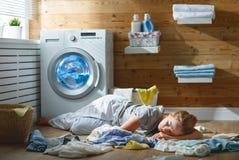 Zmęczona gospodyni domowej kobieta w stresie śpi w pralnianym pokoju z obmyciem obraz royalty free