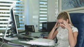 Zmęczona i śpiąca młoda biznesowa kobieta przy biurkiem z laptopem zdjęcie stock