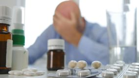 Zmęczona i Chora osoba Utrzymuje jego głowę Z ręką z Medycznymi pigułkami na stole obraz royalty free