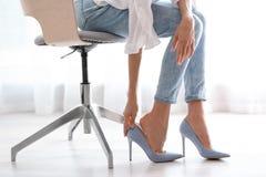 Zmęczona kobieta bierze daleko buty przy biurem obraz royalty free