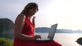 ZmÄ™czona kobieta pracujÄ…ca na laptopie i ziewajÄ…ca siedzÄ…ca na oceanie zdjęcie wideo