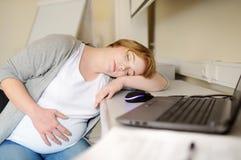 Zmęczona kobieta w ciąży śpi blisko laptopu przy jej pracującym miejscem w biurze r URLOPY MACIERZY?SCY obrazy royalty free